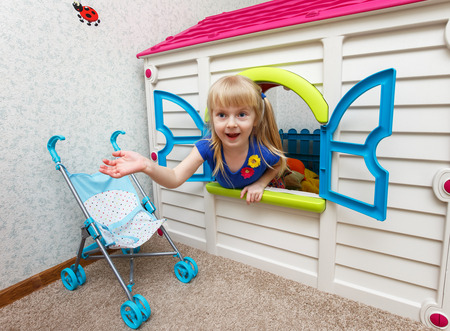 Pretty little girl looking out from toy house in daycare