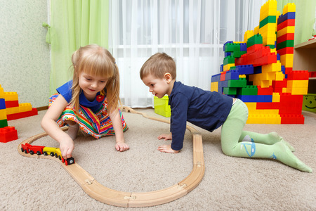 Two children play with toy railway in kindergarten Фото со стока