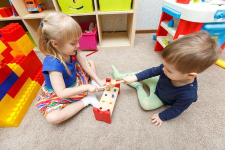 Dwoje dzieci grać z zabawek młotki i kije w przedszkolu razem