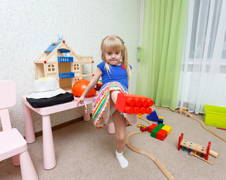 Funny little girl making trick by holding plastic block on her foot