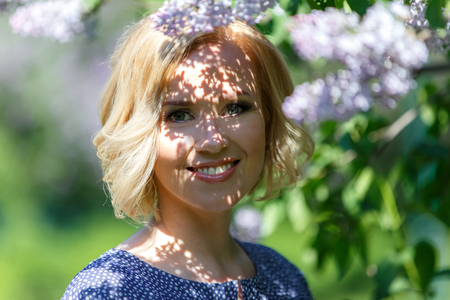 Shadows of lilac bush on the face of beautiful young woman Banque d'images