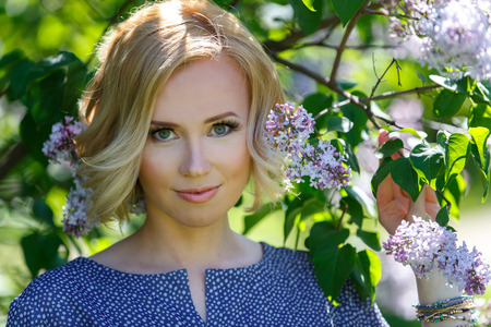 Gorgeous beautiful young blond girl near lilac bush Фото со стока