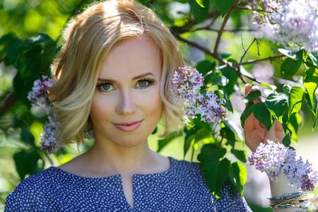 Gorgeous piękne blond dziewczyna w pobliżu krzak bzu