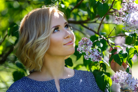 Smiling beautiful young blond girl near lilac bush Фото со стока