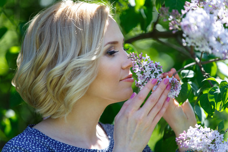 Beautiful young blond woman sniffing lilac bush