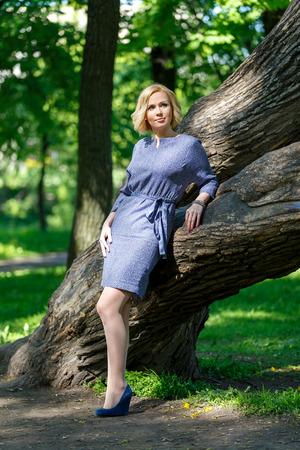 Элегантная модная молодая женщина, стоящая возле большого дерева в парке