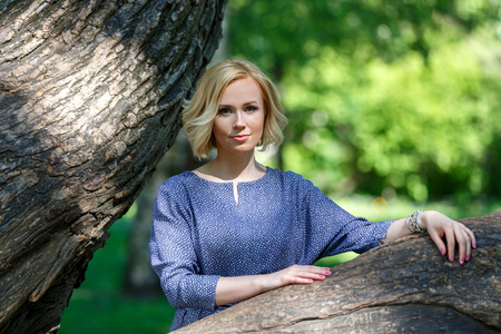 Elegant young female model leaning on big linden in the park Фото со стока