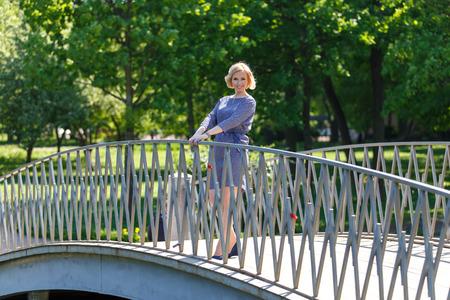 Piękna młoda kobieta, stojąca na moście w parku