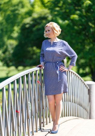 Портрет стильный молодой женщины, стоя на мосту в парке