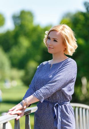 Портрет стильный молодой блондин женщина, стоящая на мосту