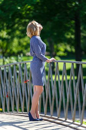 Элегантная молодая блондинка девушка, глядя на солнце на мосту