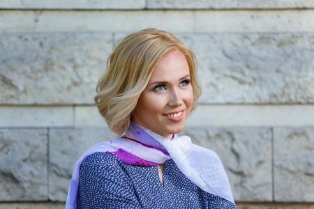 Beautiful smiling young woman near stone wall