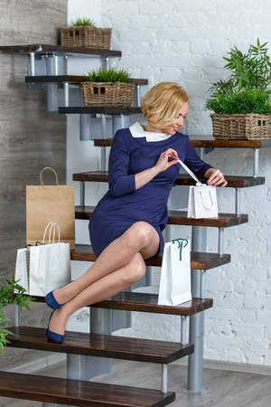 to unpack: Young blond elegant woman unpacking her shopping bags on the stairs