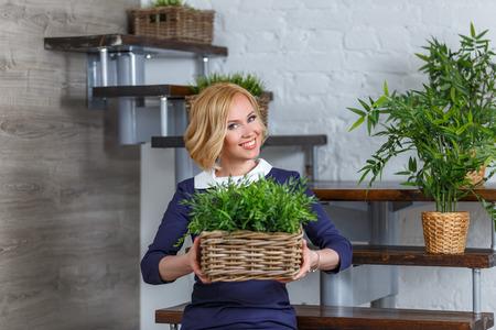 Молодая женщина улыбается, холдинг коробка с зелеными растениями. Эко-концепция. Фото со стока