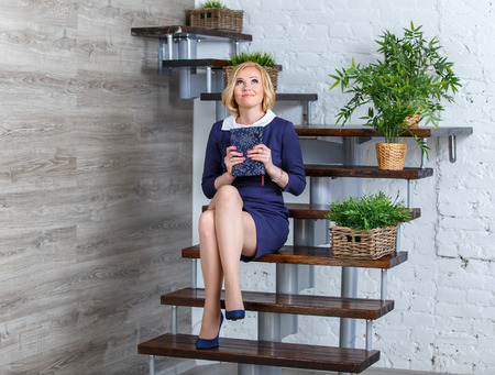 Улыбаясь молодая женщина в элегантное платье мечтает, сидя на лестнице