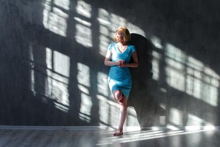 Привлекательная белокурая женщина, опираясь на стену и щурясь