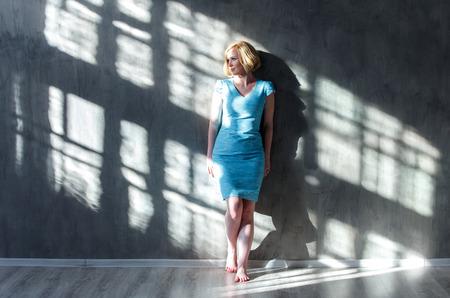Atrakcyjne blond kobieta przechylony na ścianie i patrząc na światło słoneczne