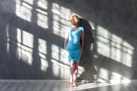 Улыбаясь блондинка женщина, опираясь на стене и глядя на солнечный свет Фото со стока