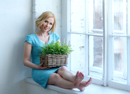 Young smiling woman sitting on windowsill with box of green plants. Eco concept.