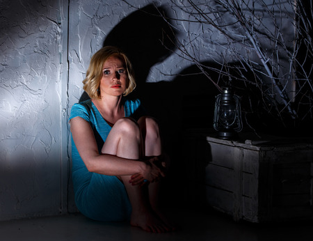 Frightened young woman with extinct lamp sitting in dark horrible place Фото со стока