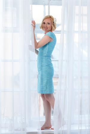 Красивая нежная девушка, стоящая за белыми занавесками Фото со стока