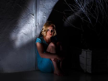 Молодая женщина в синем платье сидит в темном страшном месте