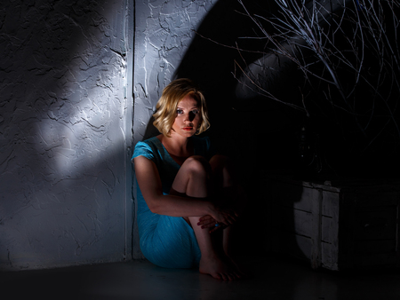 Młoda kobieta w niebieskiej sukni siedzi w ciemnym miejscu straszliwej Zdjęcie Seryjne
