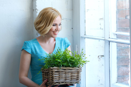 Cute smiling woman with basket with green plants looking out of the window