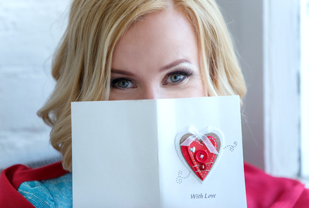Closeup of woman face partly covered with love postcard. Фото со стока