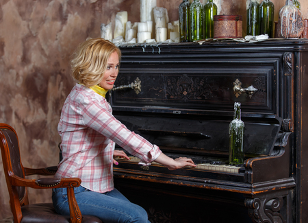 Funny young woman playing shabby retro piano