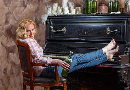 Blond woman posing near retro piano with waxed wine bottle