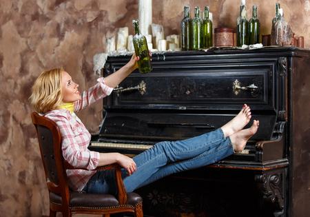 Белокурая женщина позирует в кресле с вощеной бутылкой вина возле ретро фортепиано