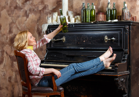 Blond woman posing in armchair with waxed wine bottle near retro piano
