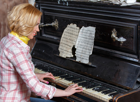 Smiling female musician playing sheet music on retro piano Banque d'images