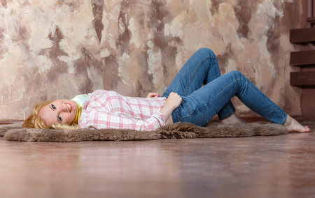 Pleased blond girl lying on a fur on the floor