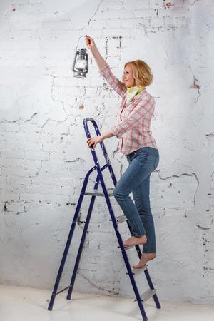 Блондинка с освещенной фонарем, стоя на стремянке