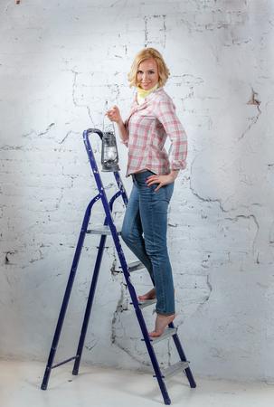 Сексуальная блондинка модель с освещенной фонарем, стоя на стремянке Фото со стока
