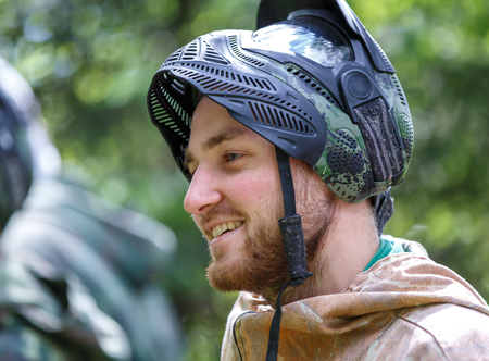 Smiling handsome young man in opened paintball mask Фото со стока