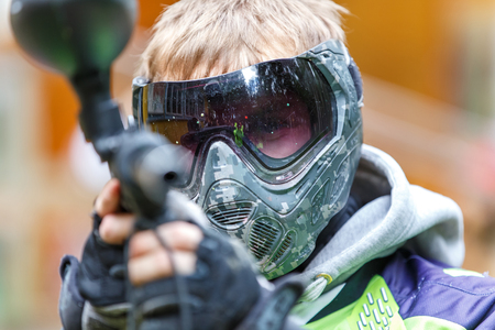 bullet camera: Handsome paintball player aiming in camera. Closeup. Stock Photo