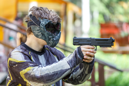 Cool shooter with handgun in paintball helmet aiming.
