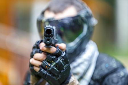 Прохладный шутер с пистолетом в шлеме пейнтбола прицеливания в камеру. Сосредоточиться на верхней части пистолета.