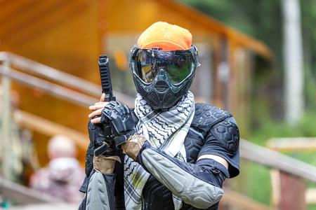Chłodny paintball fighter w specjalny pancerz farby trzymający pistolet.