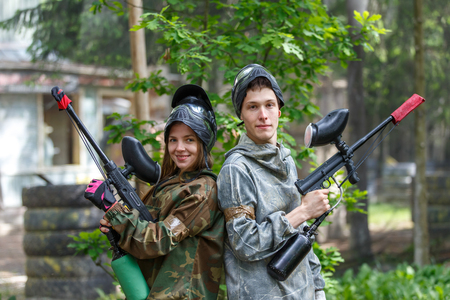 Счастливая пара позирует с пейнтбольного оружия на открытом воздухе Фото со стока