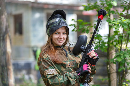 Beautiful female model posing in paintball ammunition outdoors Фото со стока