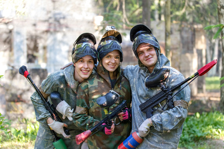 Group portrait of three smiling paintball players outdoors
