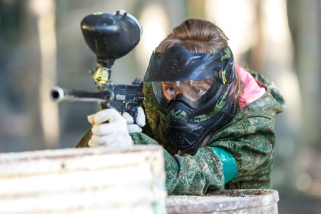 Cool girl shooting from paintball gun. Closeup. Фото со стока