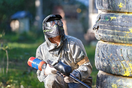 Paintball player with paint gun sitting behind fortification Фото со стока