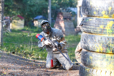 Man with sniper paintball riffle sitting in ambush Фото со стока