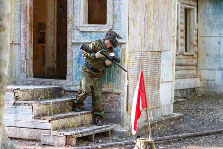 Młody człowiek w ekstremalnych szkoleń paintball z wychwytywaniem flagami. Zdjęcie Seryjne