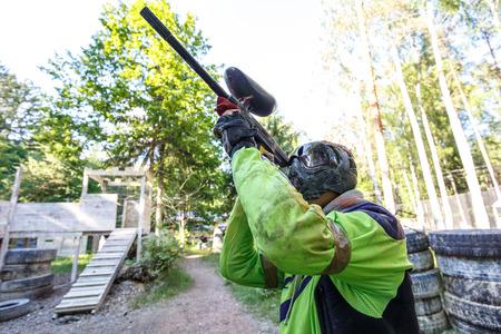 Прохладный экстремальный спортсмен стрельба из пейнтбольного маркера Фото со стока
